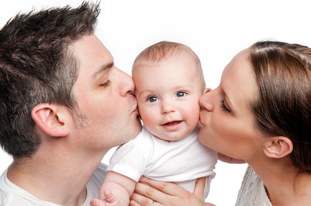 young couple hugging kissing: Young Mother Father Kissing Baby  Studio shot on white background   Stock Photo