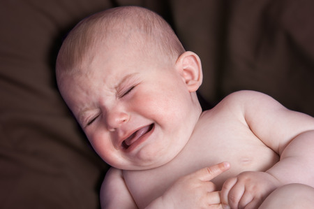 crying baby: Crying baby distressed on brown pillow