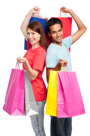 carrying girl: Teenage couple with shopping bags. Studio shot on white background. Stock Photo