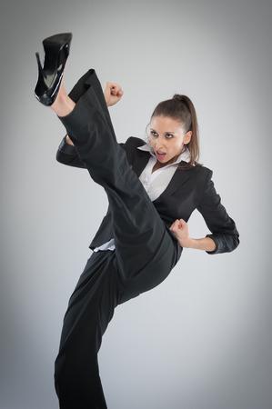 空気中に蹴るハイヒールで積極的な女性。灰色の背景のスタジオで武道空手のポーズ。