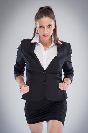 puños cerrados: Mujer elegante en la falda negro y una chaqueta va en serio.