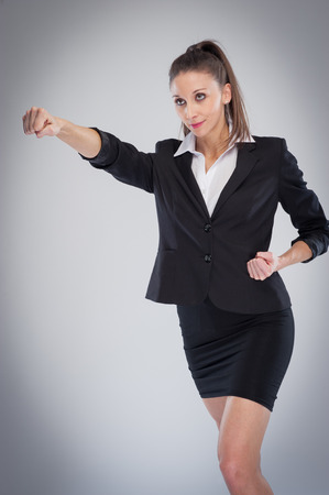 defence: Striking executive woman in a businesss suit punching the air. Posed in a studio background.