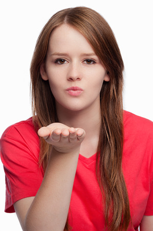 Beautiful girl in a red t-shirt blowing a kiss to camera. Hand held out flat. Studio shot on white background. Stock Photo