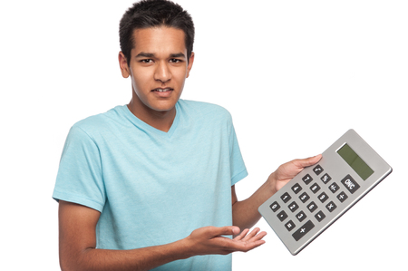 calculated: Ethnic young man with puzzled look and a big calculator. Studio shot on white background