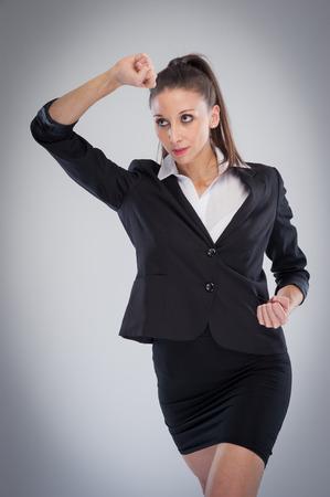 sexy secretary: Mujer en el entrenamiento con los puños cerrados haciendo una actitud del karate. Estudio disparó sobre fondo gris.