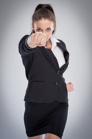 defence: Direct female corporate boss punching at camera. Pose looking straight to camera.