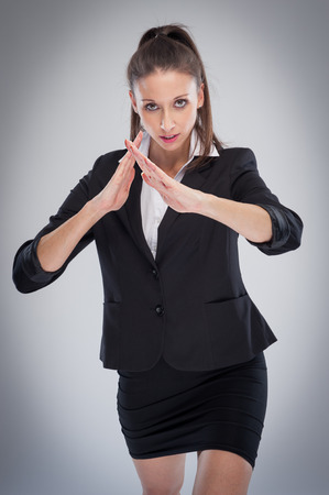 Woman in short black skirt and jacket doing a martial arts pose to camera.
