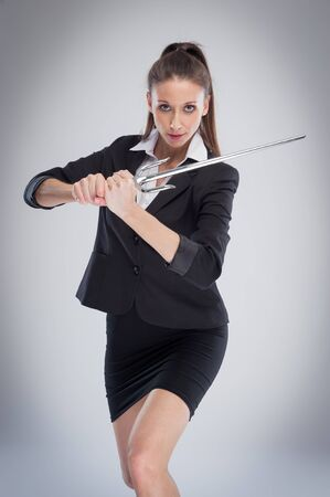 defense: Sexy woman exercise training with a steel sword. Studio shot on grey background. Stock Photo