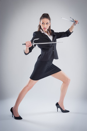 woman with sword: Woman in black suit means business. Stock Photo