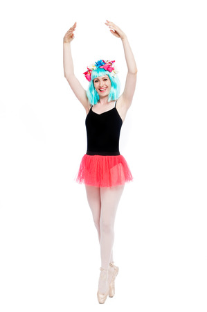 Smiling ballet girl in point position with arms up. Shot in studio on white background.