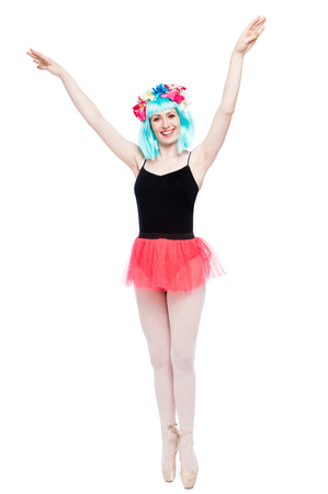 Tutu wearing ballet girl with arms up on pointy toes.