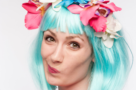 Girl with flower headband and crazy wig shot in the studio on white background.