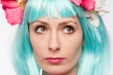 Strange girl looking up in colourful wig.