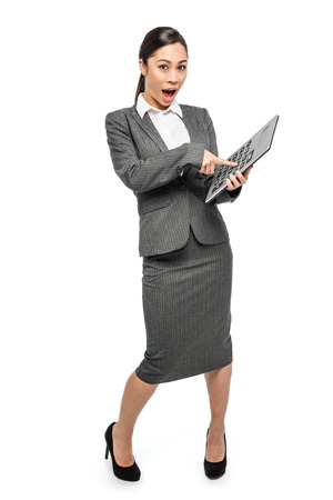 Smart woman in grey business suit pointing her finger at a big calculator. Studio shot on white background.