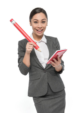 Woman with big pencil writing on red pad of paper happy expression. Studio shot on white background.