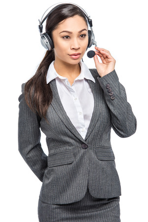 Helpful woman with headphones and microphone working in customer services. Isolated on white background in studio.