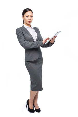 Smart executive Asian woman with a ipad tablet wearing a grey suit and shot in the studio on a white background.