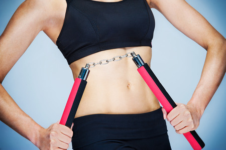 Woman working out with Nunchaku. Studio shot with red and blue.