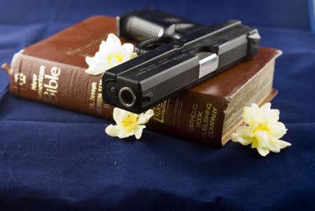 firearms: Un arma de fuego negro descansando sobre una Biblia cerrada con flores