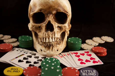 A skull surrounded by poker chips and playing cards depicting two royal flushes. photo