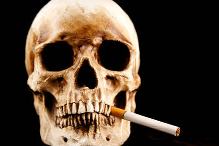 A skull on a black background with an unlit cigarette hanging from its mouth. photo