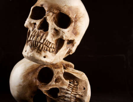 Two human skulls stacked on top of each other with a black background.