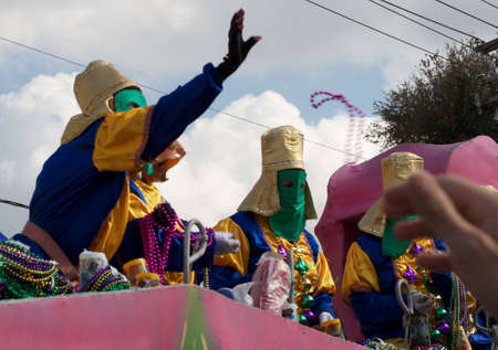 A masked rider throws beads from a float to revelers during a Mardi Gras parade in New Orleans Stock Photo - 9868012