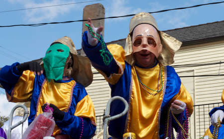 A masked rider throws beads from a float to revelers during a Mardi Gras parade in New Orleans Stock Photo - 9868016