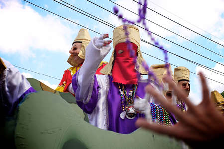 A masked rider throws beads from a float to revelers during a Mardi Gras parade in New Orleans photo