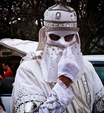 A white knight adjusts his mask while getting ready to ride in a mardi gras parade in new orleans photo
