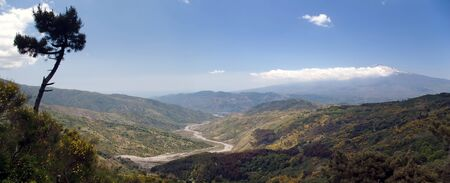 Beautiful panoramic valley of the sicilian hinterland under the majestic volcano Etna with dry river bed