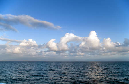 Blue sky with clouds over sea photo