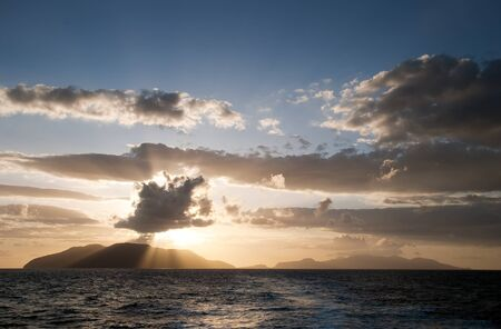 Sunrays breaking through the clouds over the sea and islands Stock Photo