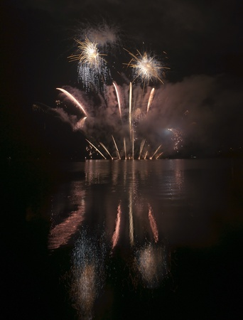 Colorful fireworks on black sky background with water reflections