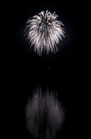 Clear white fireworks on black sky background with water reflections