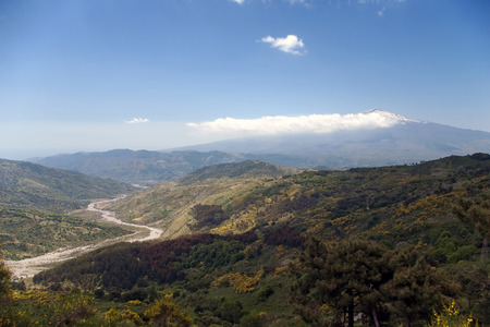 Beautiful valley of the sicilian hinterland under the majestic volcano Etna with dry river bed  photo