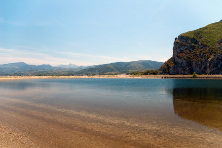 Mirrored cliff in shallow sea, mountains in background, Tindari gulf, Sicily, Italy Stock Photo