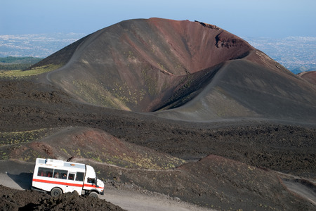Minibus on the road to Etna, with volcano in background, Sicily, Italy