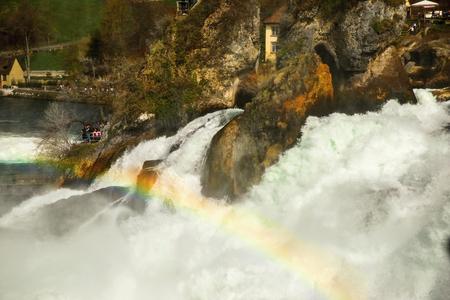 unchained: Waterfall Rheinfall in Switzerland, huge cascade of flowing water on rock with rainbow