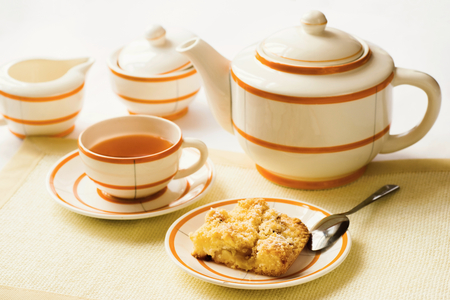 creamer: Vintage white tea set with orange stripes, cup of tea, teapot, sugar bowl and creamer and small plate with traditinal crumble pie for teatime, on light yellow and white background