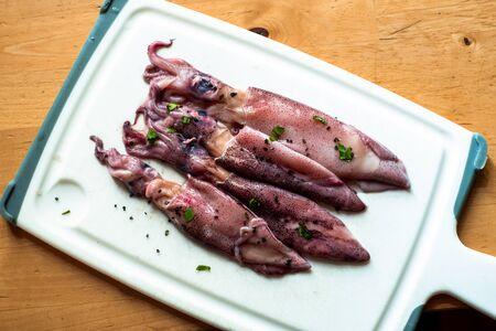 Raw calamari on white kitchen board on wooden table. 写真素材