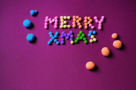 Inscription Merry Christmas assembled from small colorful polyester pompons on violet background.
