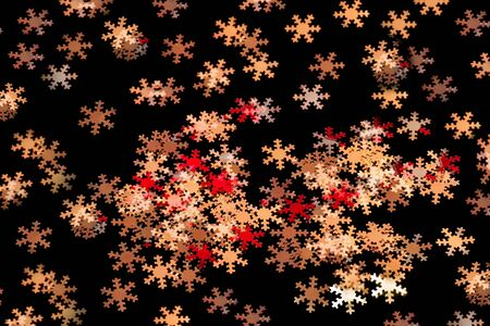 Many tiny yellow, red,beige, brown and silver snowflakes on black background, seamless. Christmas decoration, can be used e.g. as wrapping paper or wallpaper. Banco de Imagens