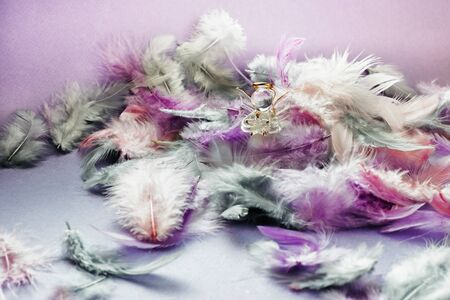 Christmas still life with pink and violet feathers and glass guardian angel figurine. Zdjęcie Seryjne