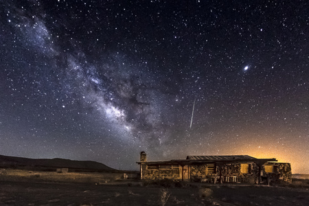Milky Way, Meteor, and Abandoned Home in the desert Editorial
