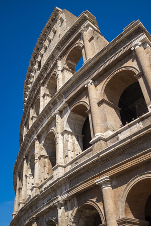 Detail of the wall of the Colosseum Rome, Italy showing the tiers of arches on the amphitheatre against a sunny blue sky Stock Photo