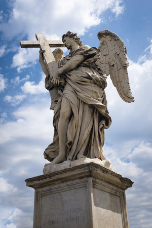 The historic Angel with Cross Statue in travertine marble on Pont Sant Angelo, Rome, Italy against a cloudy blue sky Фото со стока