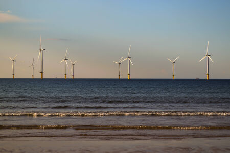 An image of off shore wind turbines as seen from the beach photo