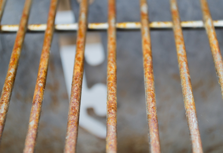 Rusted metal grill bars pictured vertically showing signs of deterioration