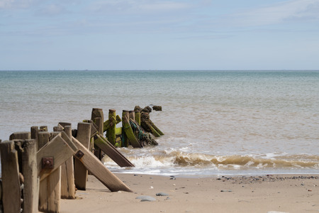 Standing on the coastline following wodern groynes into the sea